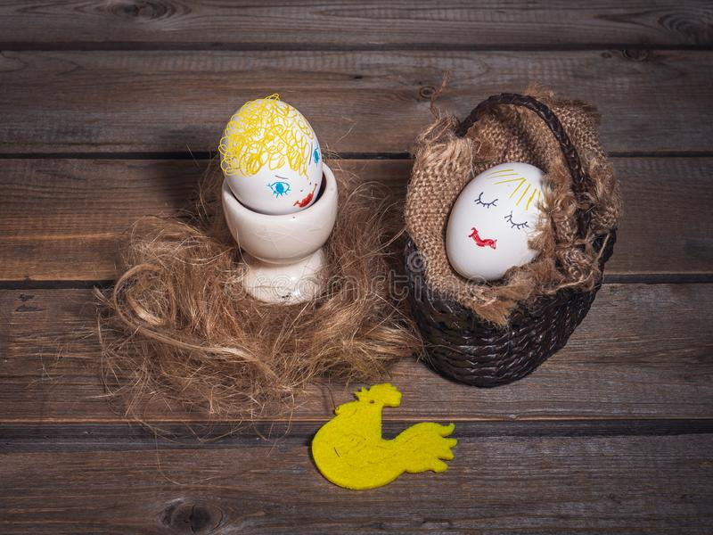 Two funny eggs with painted faces on wooden background. Easter card royalty free stock photo