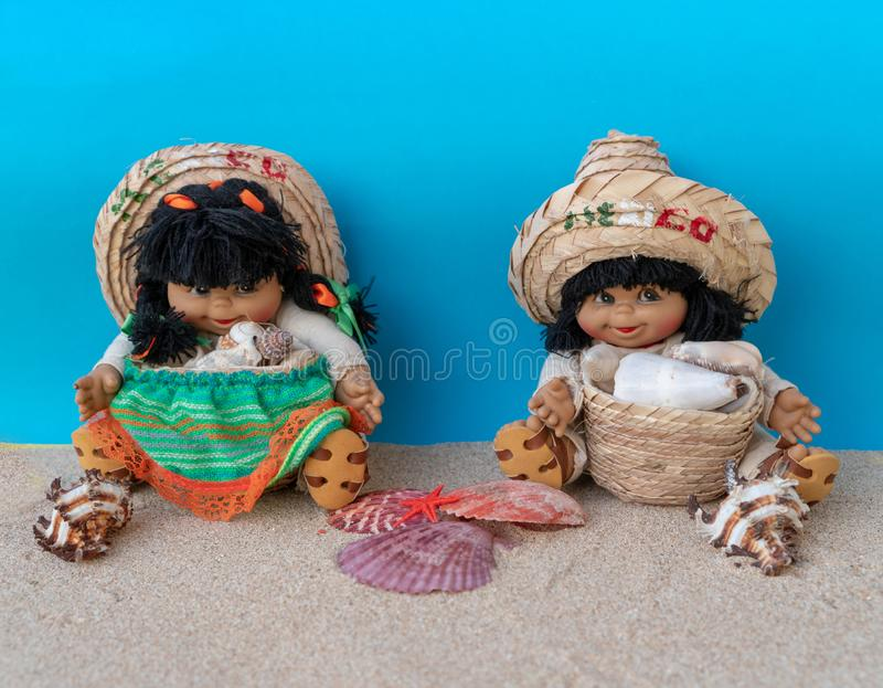 Two funny figures Mexican boy and Mexican girl on the sand on a blue background. Hello mexico concept stock photography