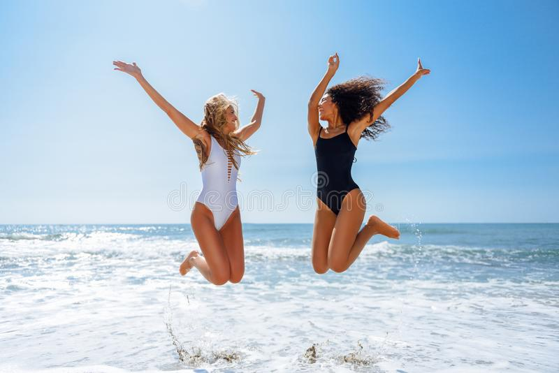 Two funny girls in swimsuit jumping on a tropical beach stock images