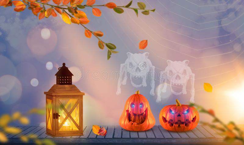 Two funny halloween pumpkins with spooky ghosts over their heads on wood with autumn branches and spider web in the background. Funny orange halloween pumpkins stock photography