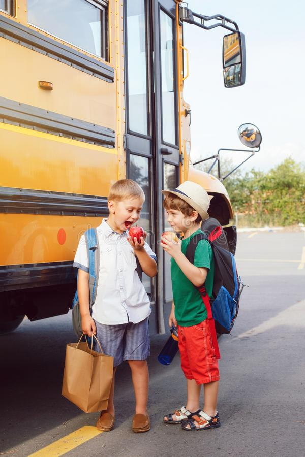 Two funny happy Caucasian boys students kids eating apples near yellow bus on 1 September day. stock image