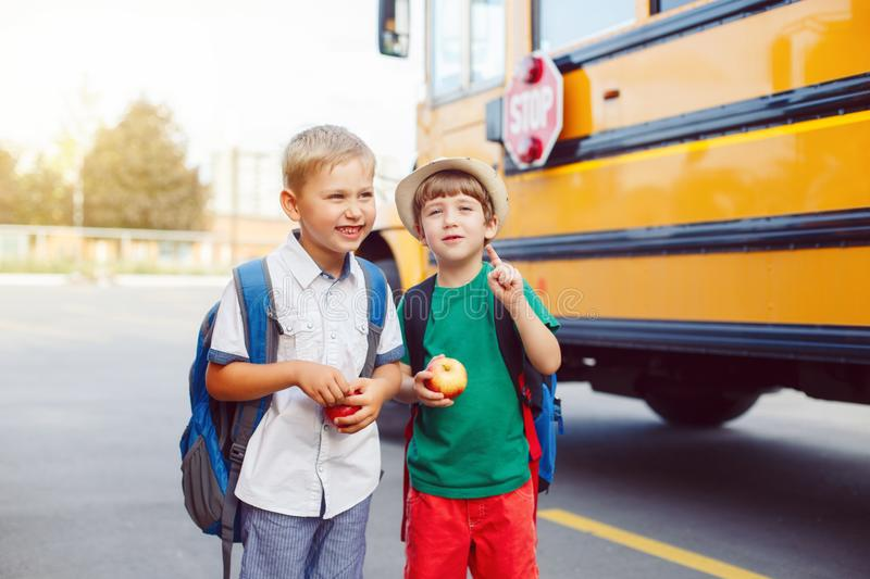 Two funny happy Caucasian boys students kids near yellow bus on 1 September day stock images