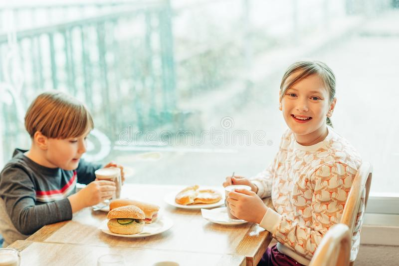 Two funny kids drinking hot chocolate in cafe stock photography