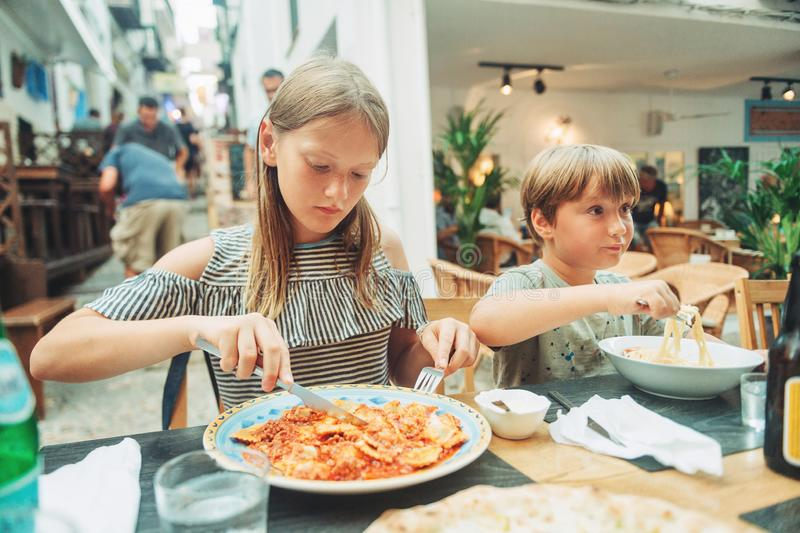 Two funny kids having lunch in the restaurant. Eating ravioli and pasta stock photos