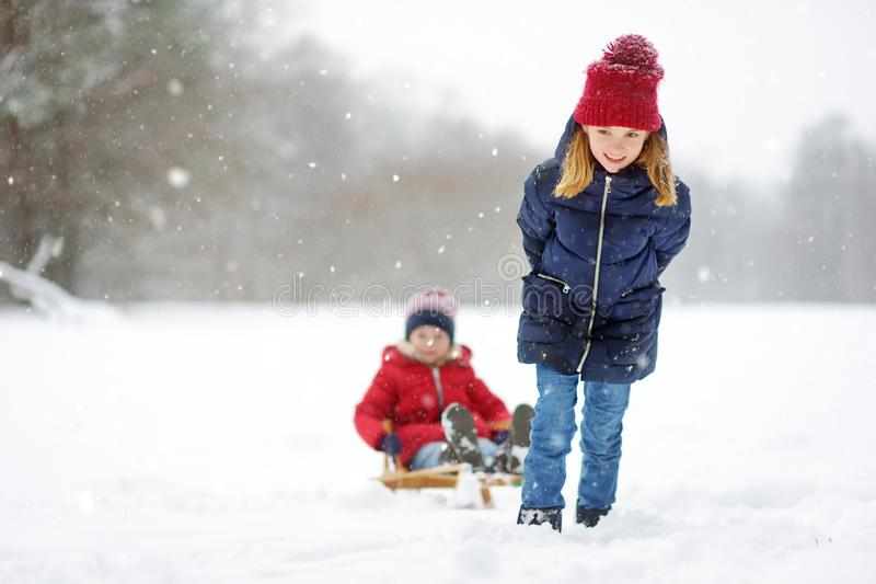 Two funny little girls having fun with a sleigh in beautiful winter park. Cute children playing in a snow. stock photos