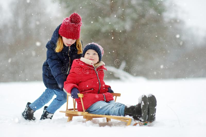 Two funny little girls having fun with a sleigh in beautiful winter park. Cute children playing in a snow. Winter activities for kids royalty free stock images