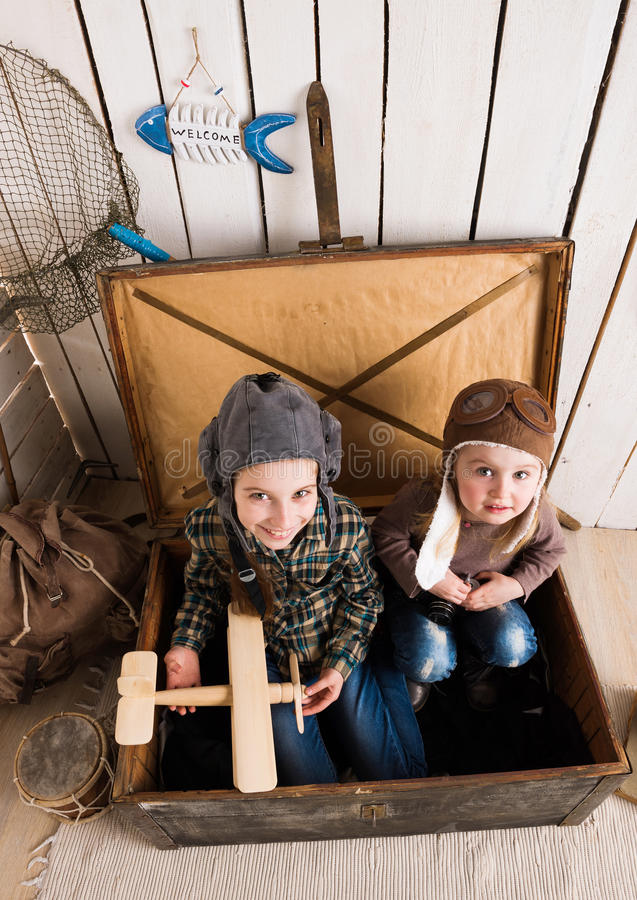 Two funny little girls inside big wooden chest. Two funny little girls in hats inside big wooden chest, photo from above stock images