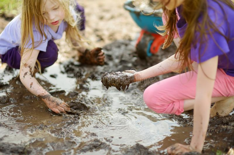 Two funny little girls playing in a large wet mud puddle on sunny summer day. Children getting dirty while digging in muddy soil. Messy games outdoors royalty free stock image