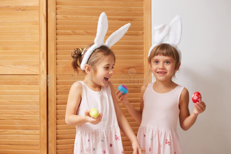 Two funny little sisters in the dresses with white rabbit`s ears on their heads have fun with dyed eggs in their hands. On the background of wooden doors stock photo