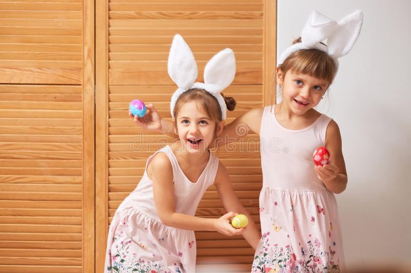 Two funny little sisters in the dresses with white rabbit`s ears on their heads have fun with dyed eggs in their hands. On the background of wooden doors royalty free stock photo