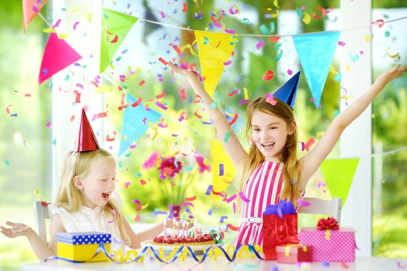 Two funny little sisters having birthday party at home, blowing candles on birthday cake. Kids birthday party with colorful decorations, gifts and banners stock images
