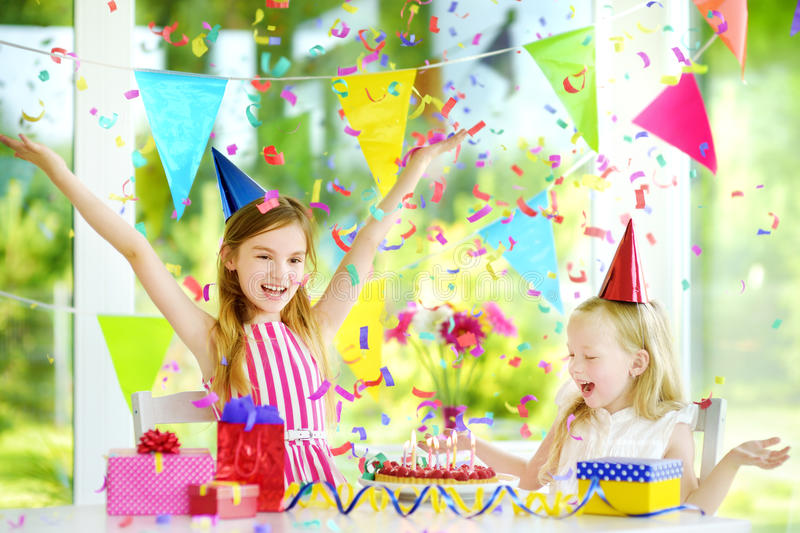 Two funny little sisters having birthday party at home, blowing candles on birthday cake. Kids birthday party with colorful decorations, gifts and banners royalty free stock image