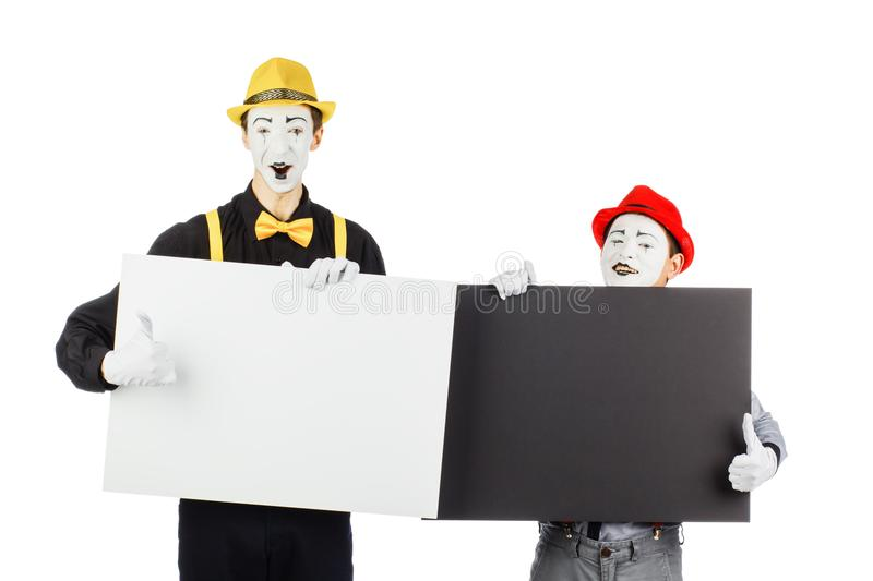 Two funny mimes holding a white blank on a white background. stock photo