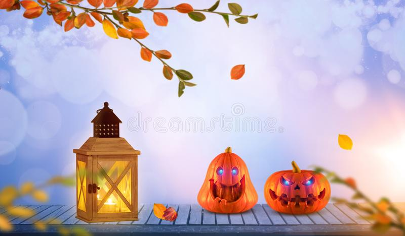 Two funny orange pumpkins with glowing eyes on wood. Bokeh and lens flares. royalty free stock image