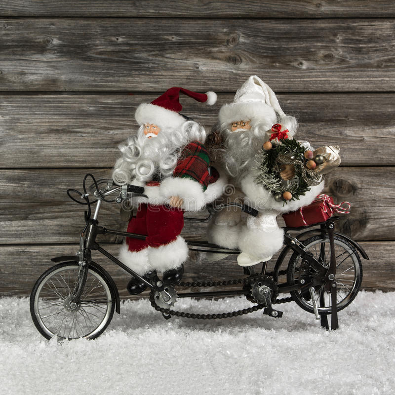 Two funny santa claus on a tandem in hurry for christmas shopping. stock photo