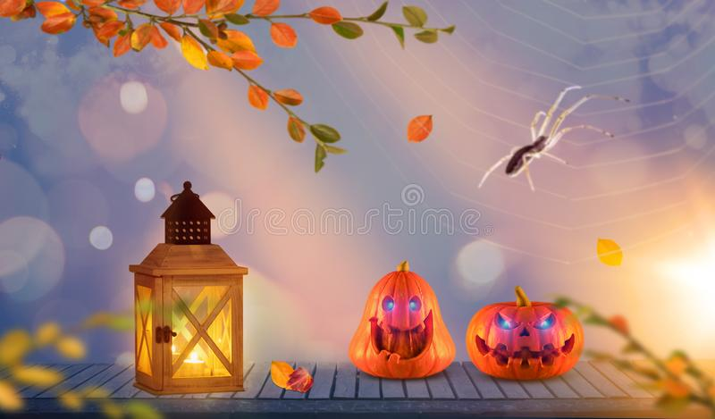 Two funny scary orange halloween pumpkins with glowing eyes onh wood with lantern with spider and a spider web in the background royalty free illustration