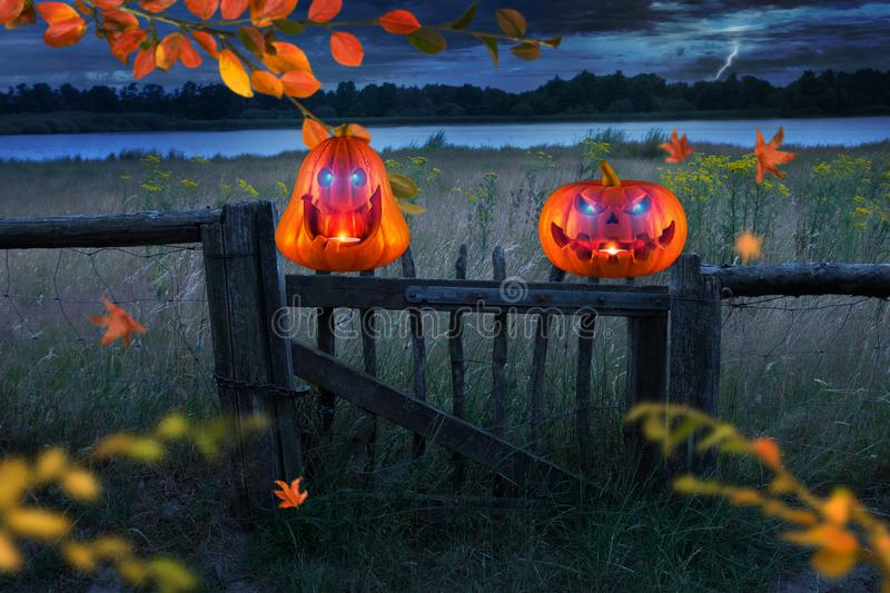 Two funny scary orange pumpkins with glowing eyes on wooden fence at halloween thunderstorm night stock photos