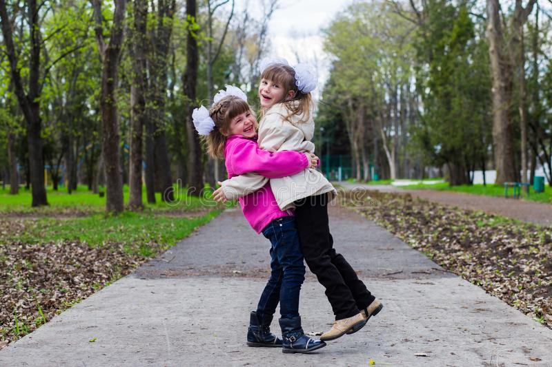 Two funny siblings sister hugging with each other while walk in park. Having fun together, positive emotions, bright colors. Copy space royalty free stock photography