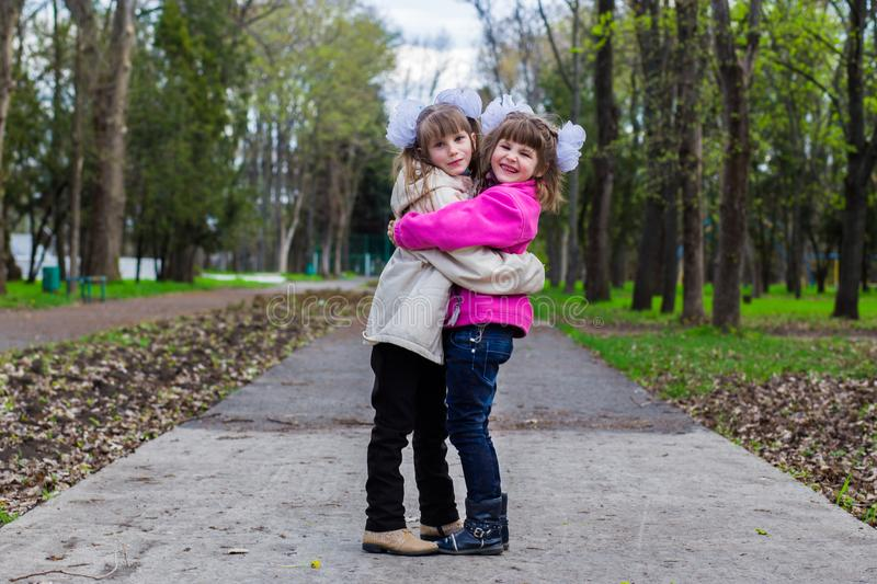 Two funny siblings sister hugging with each other while walk in park. Having fun together, positive emotions, bright colors. Copy space royalty free stock photos