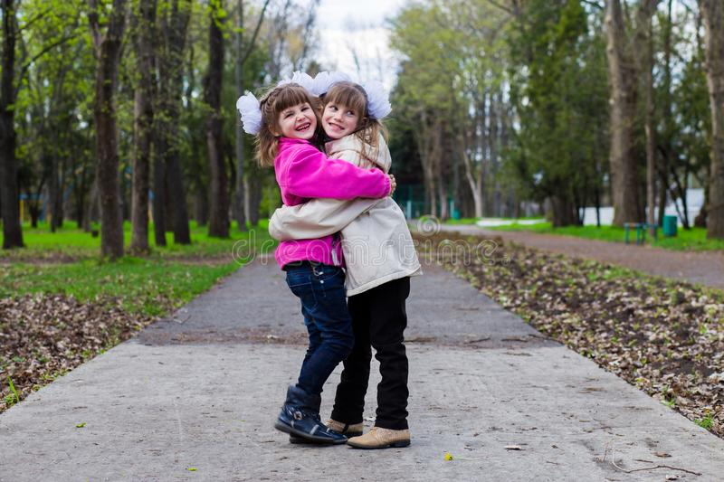Two funny siblings sister hugging with each other while walk in park. Having fun together, positive emotions, bright colors. Copy space stock image