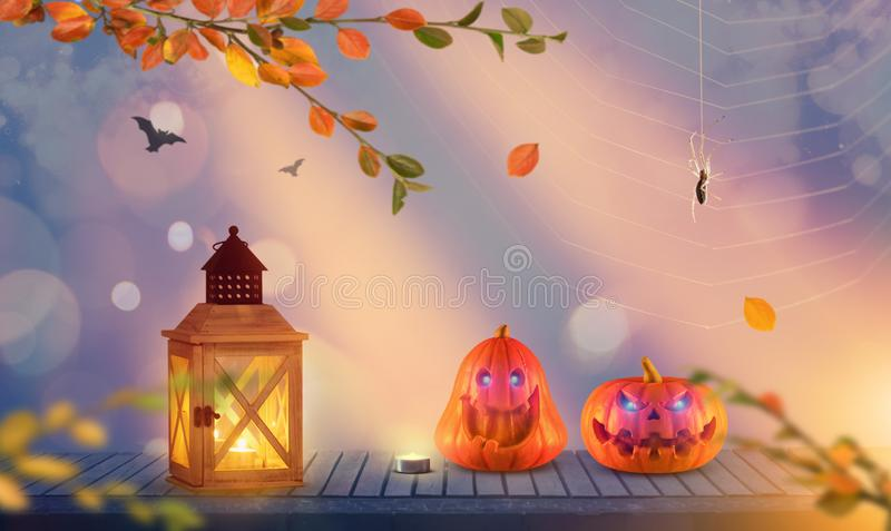 Two funny spooky halloween pumpkins with spider and bats in the background. royalty free stock image