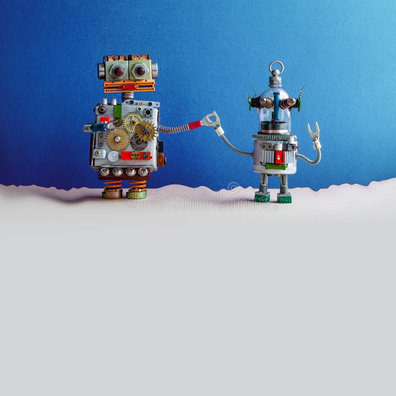 Two funny toy robots holding hands. Fantastic blue beige landscape. The big robot holds the hand of a small glass head. Robotic ufo humanoid. Copy space stock photos