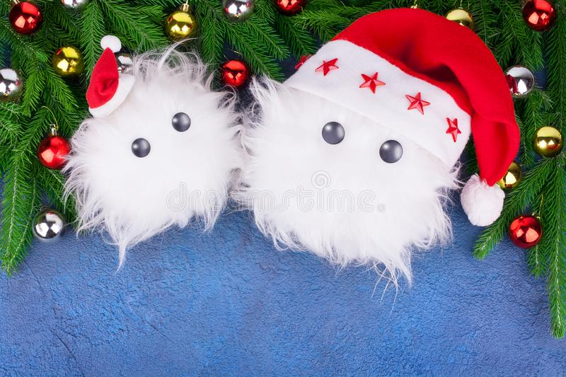Two funny white furry snow man toys in red Santa Claus hats, green fir branches on blue background, cute little Yeti or snowflakes royalty free stock photography