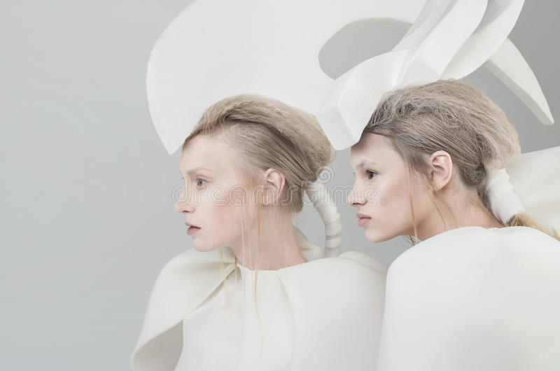 Two futuristic blonde women in white outfit over w royalty free stock images