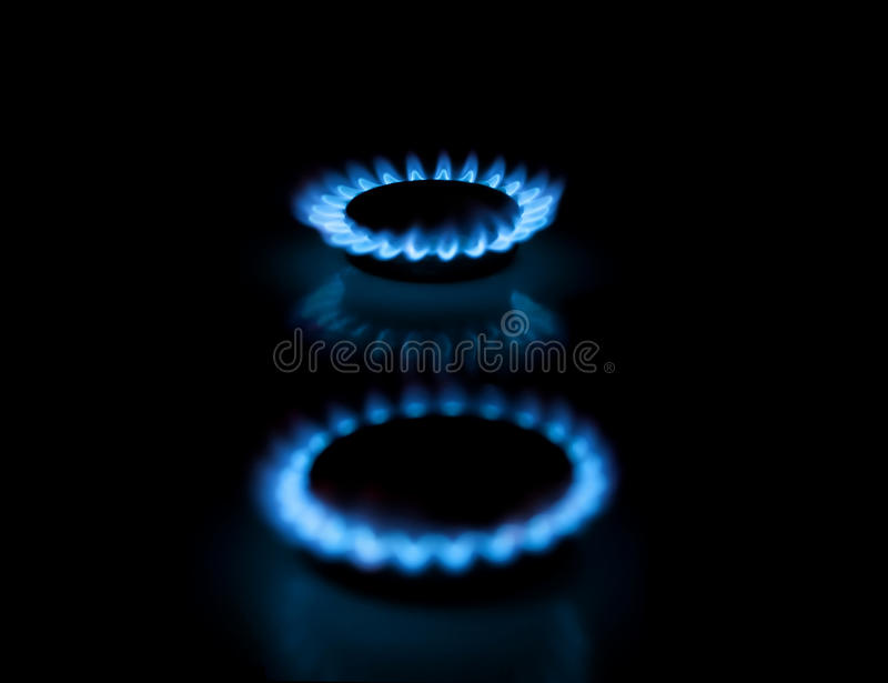 Two gas burners with flames on dark background
