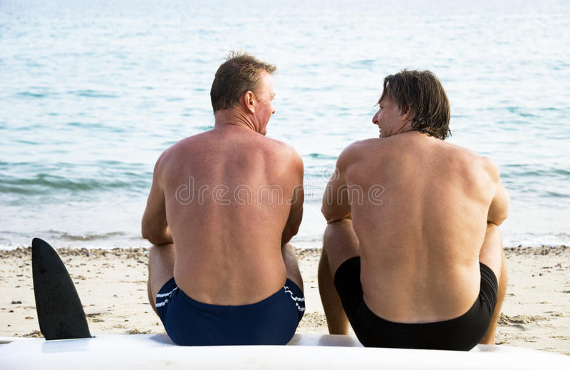 Two gay men. Two mature sporty gay men are sitting on a surboard and chatting during a day at the beach