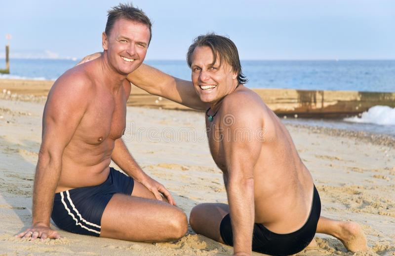 Two gay men on beach. stock images