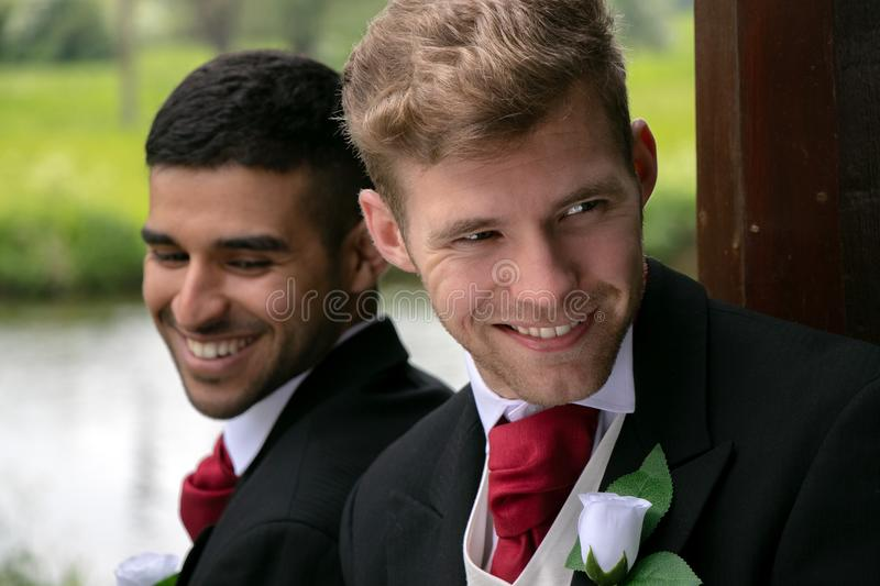 Gay couple of grooms pose for photographs by a lake on their wedding day royalty free stock image