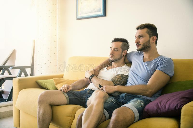 Two gay men on sofa embracing at home stock photography