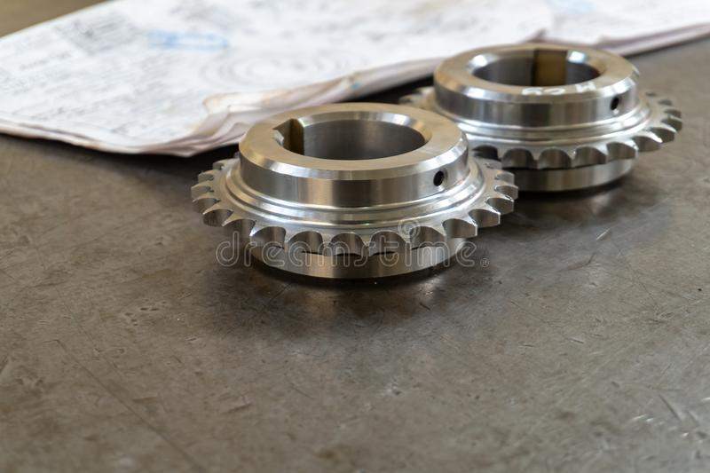 Two gears lie on a testing table with technical drawings.  stock photography