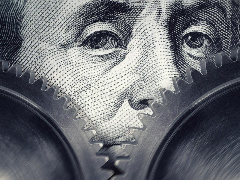 Two gears rotate on the background of hundred dollar bills. royalty free stock image
