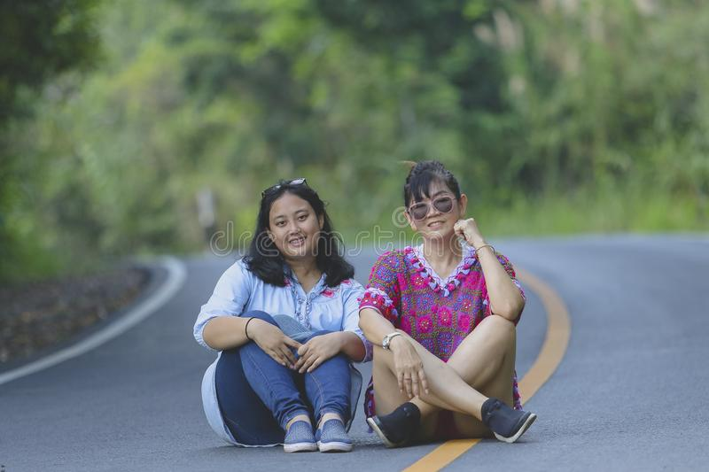 Two generation of asian woman sitting on asphalt road in khao ya stock image
