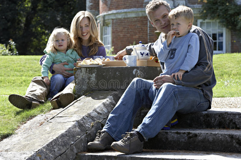 Two generation family sitting on steps in garden, having tea and sandwiches, smiling, portrait royalty free stock image