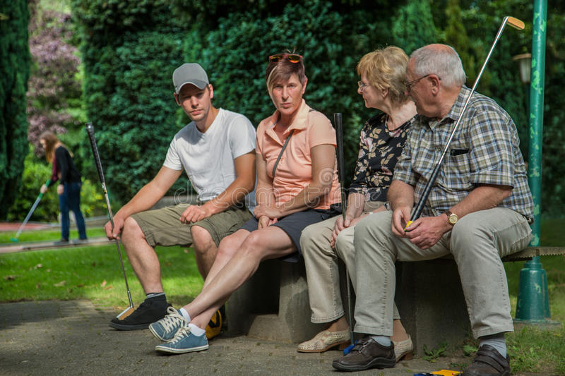 Two generation of peoples are sitting on a park bench at a minigolf court. They are waiting that they can use the court.. royalty free stock photo