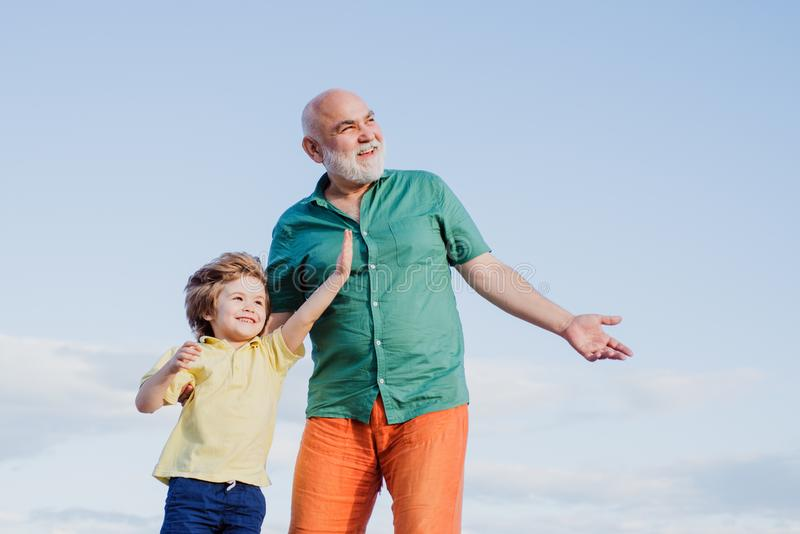 Two generation - weekend together. Two different generations ages: grandfather and grandson together. Fathers day. Happy. Father and son on meadow in summer royalty free stock images