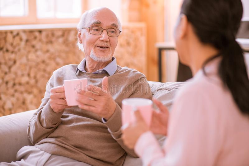 Pleased mature man talking with his nurse. Two generations. Cheerful bearded men keeping smile on his face while having pleasant conversation royalty free stock image