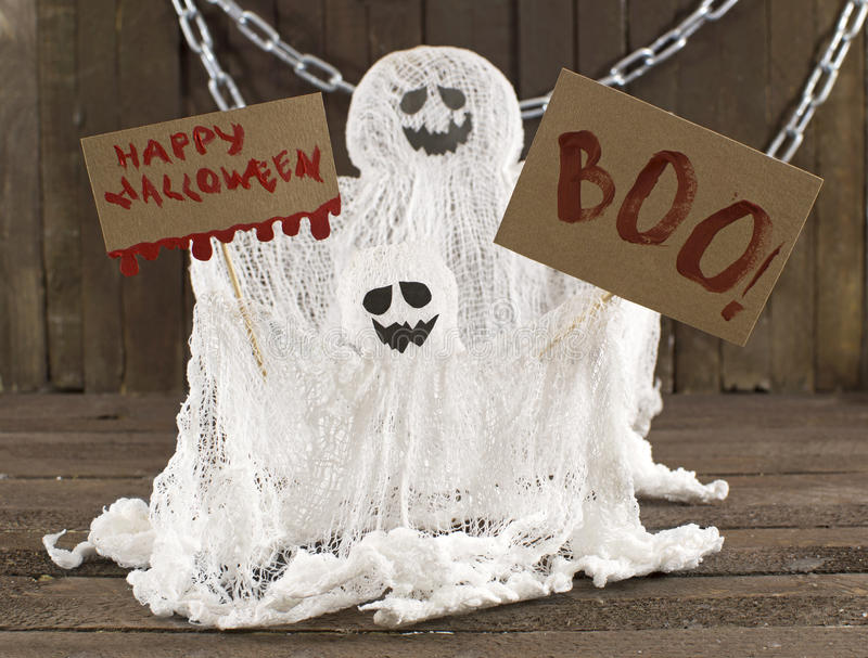 Two ghosts with banners. Halloween still life with two ghosts with chains and holiday banners on wood stock photos