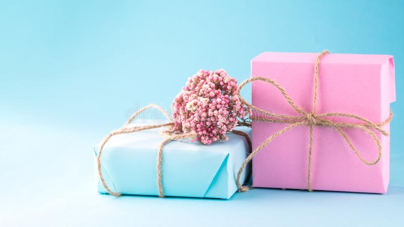 Two gift boxes of pink and blue decorated with flowers on a blue background royalty free stock photo