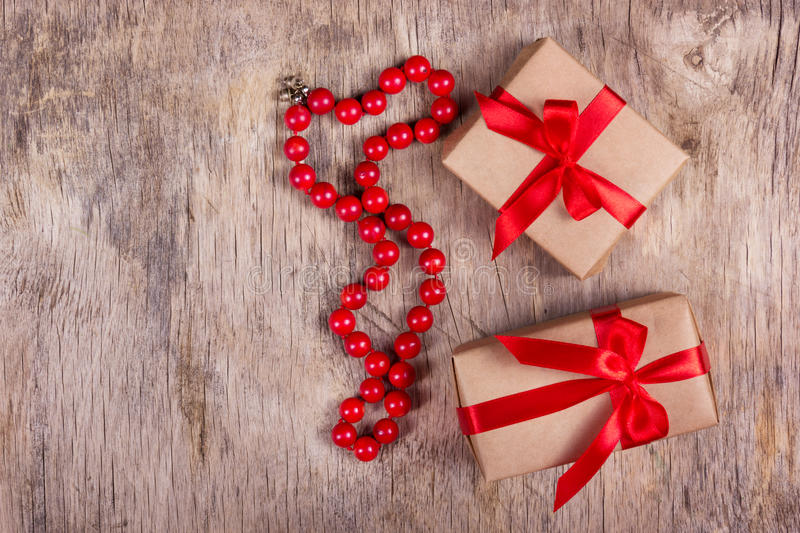 Two gift boxes with red ribbon and beads of red coral on the old wooden background. Holiday concept. Copy space stock photo