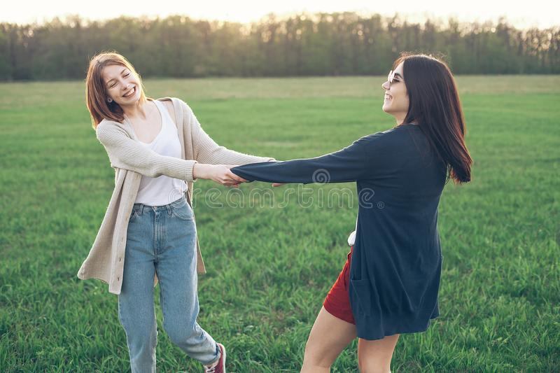 Two girl dancing on the green field royalty free stock images