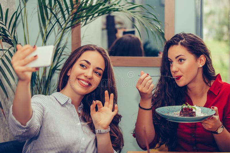 Two girl eating cakes and taking selfie with smartphone in cafe. Two beautiful young women enjoying cake together and showing OK gesture while taking selfie with royalty free stock photos
