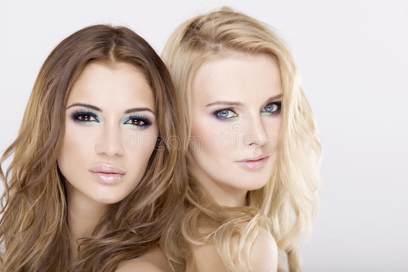 Two girl friends - blond and brunette stock images