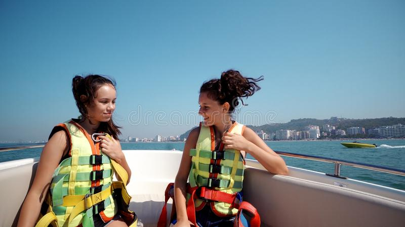 Two girl friends doing silly freestyle dance on yacht cruise. Hands up, travel vacation adventure concept stock photos