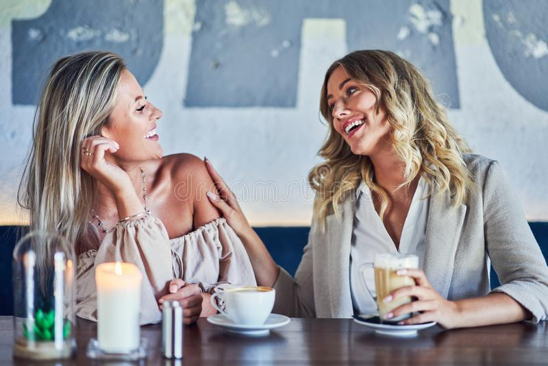 Two girl friends eating lunch in restaurant. Picture of two girl friends eating lunch in restaurant stock images