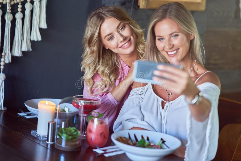 Two girl friends eating lunch in restaurant and using smartphone. Picture of two girl friends eating lunch in restaurant royalty free stock photography