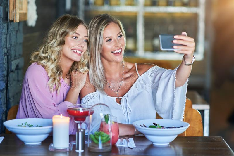 Two girl friends eating lunch in restaurant and using smartphone. Picture of two girl friends eating lunch in restaurant royalty free stock photos